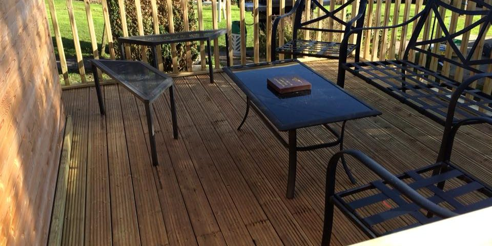 Wooden decking with black table and chair set
