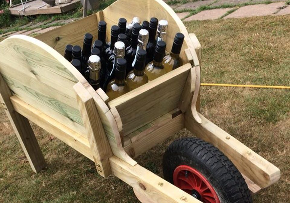 Wooden wheelbarrow holding bottles of wine